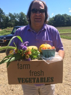 A happy CSA member carrying his bounty